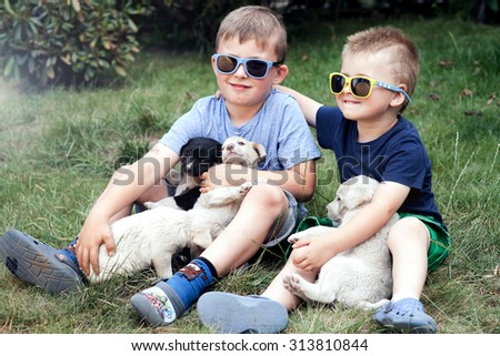 Two little brothers playing outdoor with puppies, smiling. Summer day. - stock photo