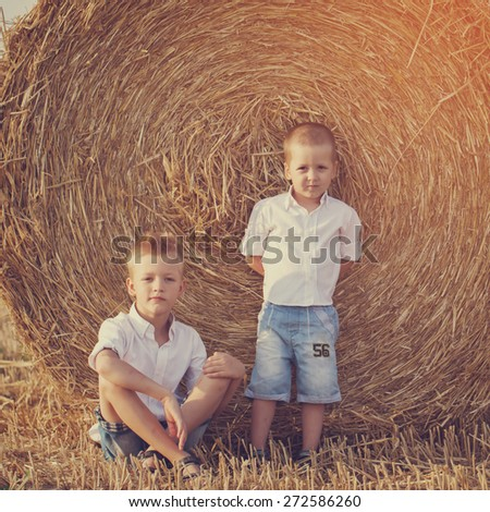 Two little brothers sitting near a haystack in wheat field on warm and sunny day, toned image