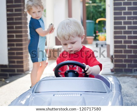 Two little brothers toddlers playing with big toy car in summer garden with focus on baby boy