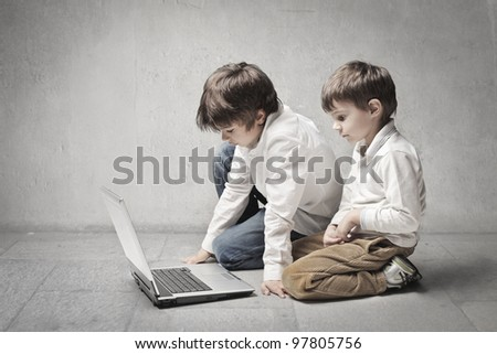 Two little brothers using a laptop