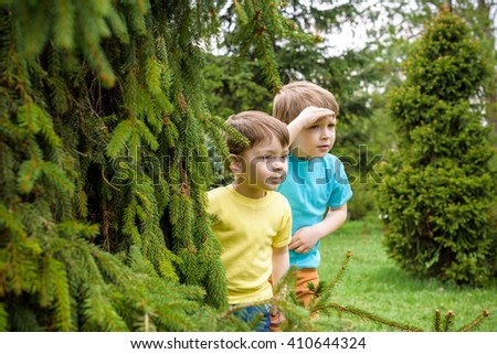 Two little caucasian brother boys playing outdoor in the park near trees on summer or spring. Surprised happy smiling faces. Selective focus on boy - stock photo