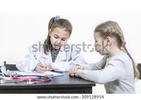 Two little Caucasian girls playing doctor and patient, white background