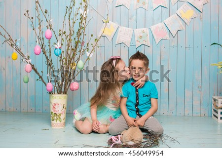 Two little child, boy, girl, brother and sister along with rabbit sitting on the floor kiss in bright blue clothes Easter, eggs, festive mood, emotion and smile surprise holiday celebration