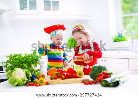 Two little children, adorable toddler girl in red chef hat and apron and funny baby boy preparing healthy lunch making delicious salad with fresh vegetables and garden herbs in a white sunny kitchen - stock photo