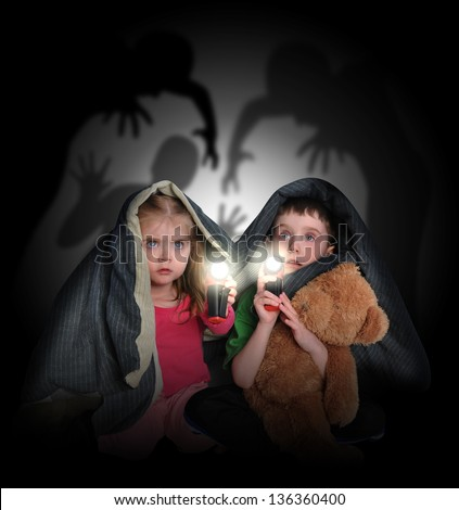 Two little children are hiding under a blanket looking at black scary monster ghosts in the background with flashlights. - stock photo