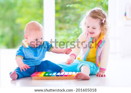 Two little children - cute curly toddler girl and a funny baby boy, brother and sister playing music, having fun with colorful xylophone at a window; kids early development class - stock photo