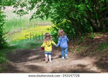 Two little children go hand in hand down on a forest road to the lake - stock photo