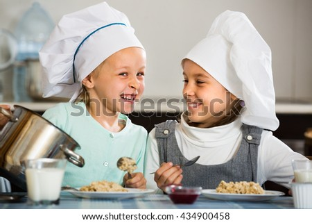 Two little children having breakfast with oatmeal porridge indoors - stock photo