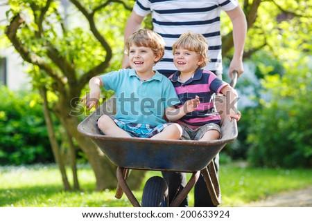 Two little children having fun in a wheelbarrow pushing by father in summer garden - stock photo