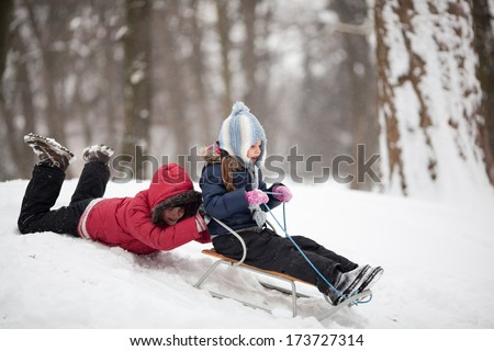 Two little children having fun using sled in a park - stock photo