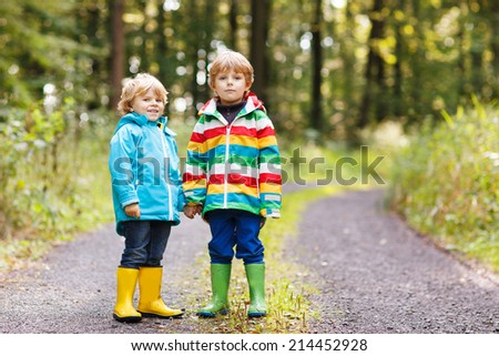 Two little children in colorful waterproof raincoats and rubber boots walking through autumn forest together. - stock photo
