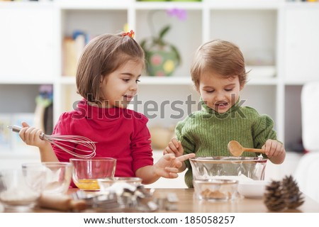 Two little children making cookies.