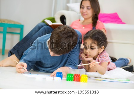 Two little children painting with colorful paints at home - stock photo