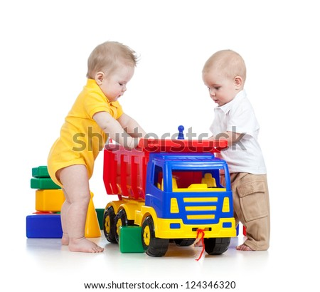 two little children playing together with color toys - stock photo