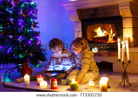 Two little children sitting by a fireplace at home on Christmas time. Happy cute adorable toddler boys, blond twins playing with new tablet gift. Family celebrating xmas holiday