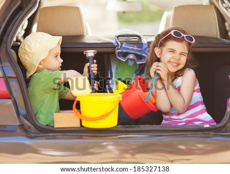 Two little children sitting in th back seat, traveling on summer vacation. - stock photo