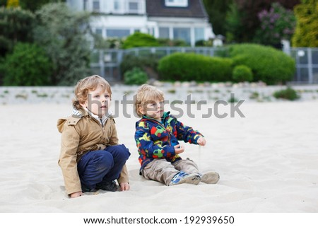 Two little children sitting on beach of river Elbe and playing together with sand on cold day, outdoors. Selective focus. - stock photo