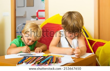Two little children sketching on paper in home interior - stock photo