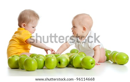 Two little children with green apples isolated on white background - stock photo