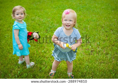 Two  little cute child girls on nature playing with a toy