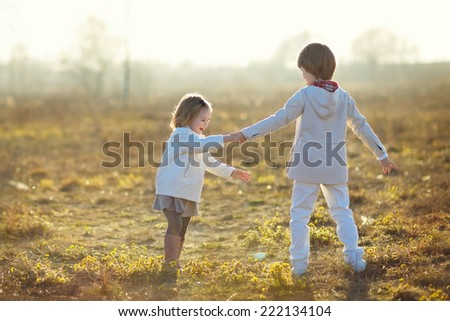 Two little cute children playing in the field on a cool summer day. Happy family. - stock photo