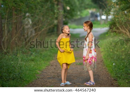 Two little cute girlfriends animatedly talking in the Park.
