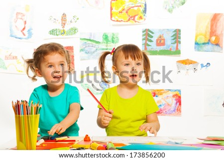 Two little cute girls painting on creative class in kindergarten - stock photo