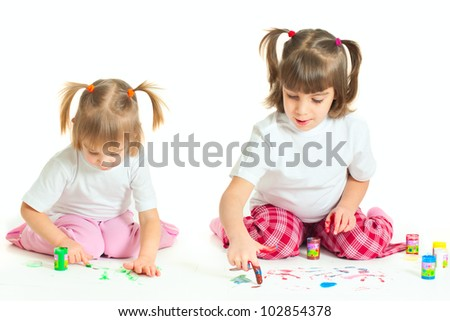 Two little cute girls (sisters) painting (isolated on white background)