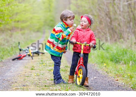 Two little cute smiling kids in bright jackets walking together in a forest on a rainy day with bikes. Friendship between siblings. Happy family concept  - stock photo