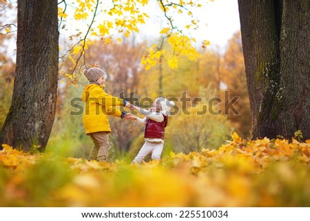 Two little cute smiling kids in bright jackets walking together in a park on a sunny autumn day. Friendship between siblings. Happy family concept  - stock photo