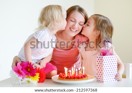 Two little daughters kissing their mother wishing her a happy birthday - stock photo