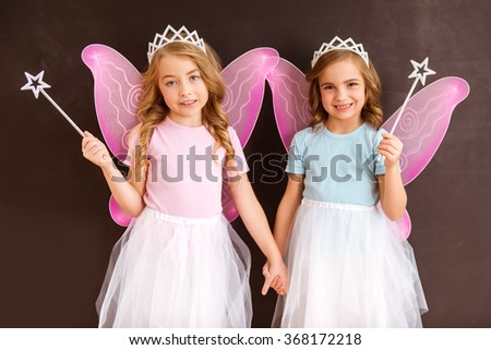 Two little fairies, one in a pink shirt, the other in the blue shirt, both with pink wings, crown and magic wands against dark background