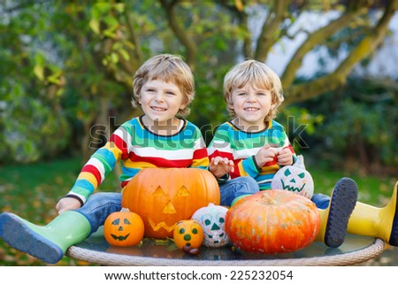 Two little friends boys making jack-o-lantern for halloween in autumn garden, outdoors. Happy family having fun together - stock photo