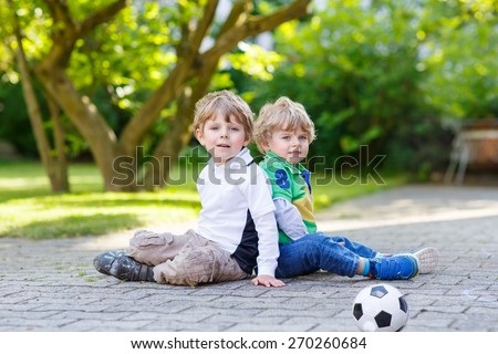 Two little friends, boys playing soccer and football and having fun, outdoors. Active leisure with children on warm sunny summer day. - stock photo