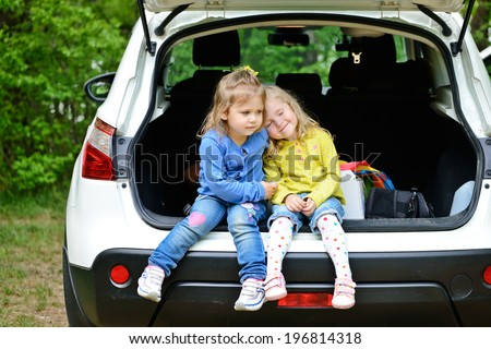two little friends girls having fun in the car - stock photo
