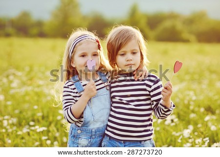 two little friends girls in the field with daisies