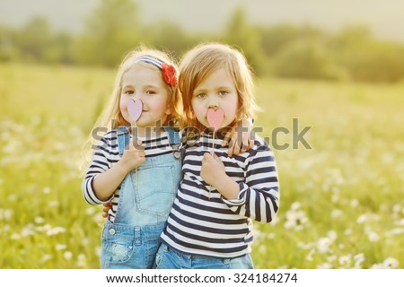two little friends girls in the field with daisies - stock photo