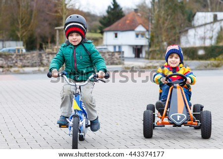 Two little friends having fun with toy race car and bicycle, outdoors. Kid boys having a competition. Outdoor games for children concept.