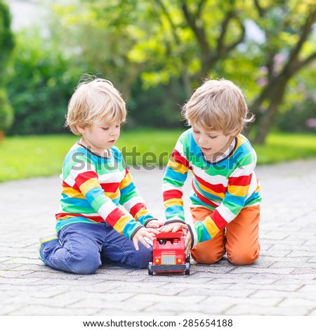 Two little friends in colorful clothing with stripes playing with red wooden bus toy in summer garden on warm sunny day. Learning to play and communicate together. - stock photo