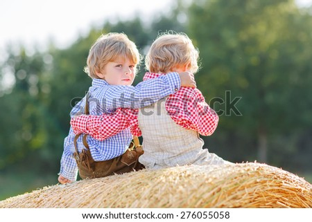 Two little friends sitting on hay stack or bale and speaking on yellow wheat field in summer. Children wearing traditional bavarian clothes. - stock photo