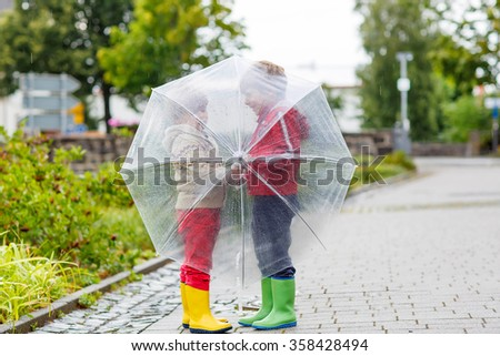 Two little friends with big umbrella outdoors on rainy day. Kids boys having fun and wearing colorful waterproof clothes and rain boots. - stock photo