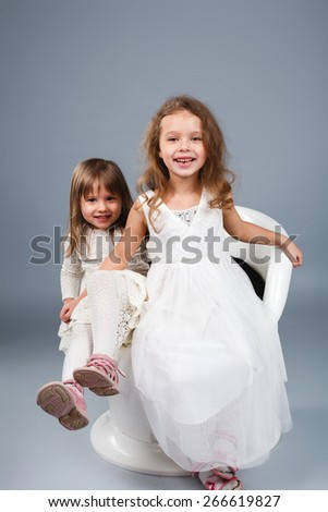 Two little funny and laughing girl in white clothes