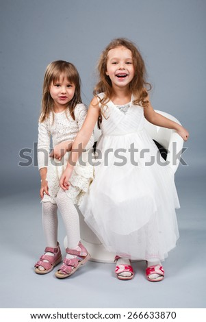 Two little funny and laughing girl in white clothes stand and hold hands.