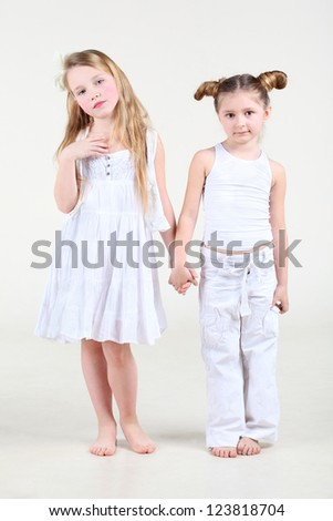 Two little funny and serious girl in white clothes stand and hold hands. - stock photo