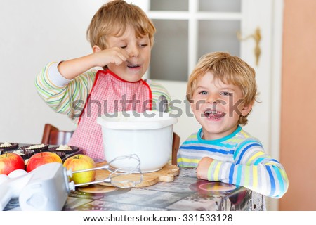 Two little funny brothers baking apple cake in domestic kitchen. Kid boys having fun with working with mixer, eggs and fruits. Children tasting dough - stock photo