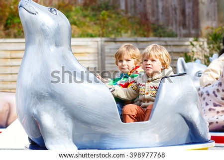 Two little funny kid boys riding on animal on roundabout carousel in amusement park. Happy children, twins having fun outdoors on sunny day. - stock photo