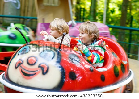 Two little funny kid boys riding on ladybug on roundabout carousel in amusement park. Happy children, friends having fun outdoors on sunny day. - stock photo
