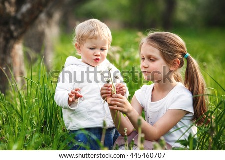 Two little girl blowing dandelions.