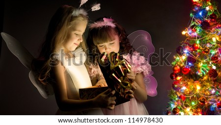 two little girl examine gift in fancy box, smile, on dark background with  Christmas-firtree - stock photo