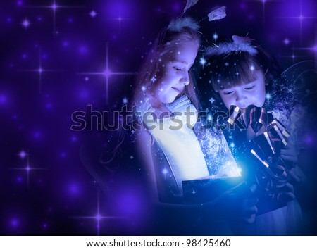 two little girl examine gift in fancy box, smile, on dark blue background - stock photo